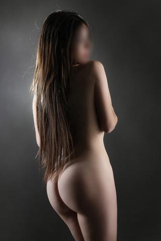 Chica morena de pelo largo de espaldas desnuda