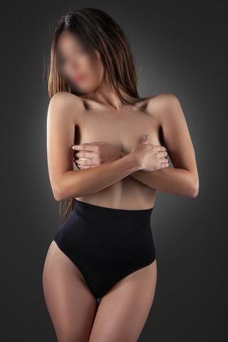 Escort tapándose los pechos desnudos