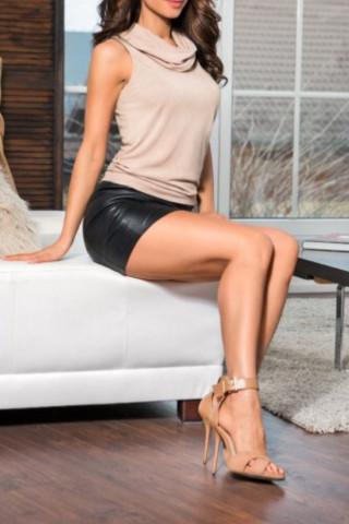 Chica elegante en top beige y falda negra