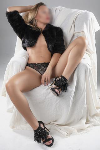 Escort rubia sensual tumbada en un sofá